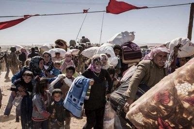 Refugiados curdos da Síria cruzam a fronteira em direção à Turquia, próxima da cidade de Kobani. Crédito: ACNUR