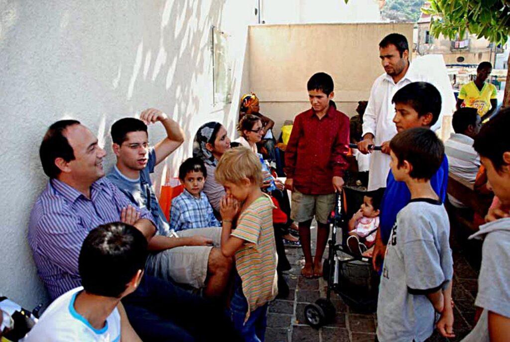 Domenico Lucano com os migrantes em Riace, Itália. Crédito: Reprodução/Adnkronos